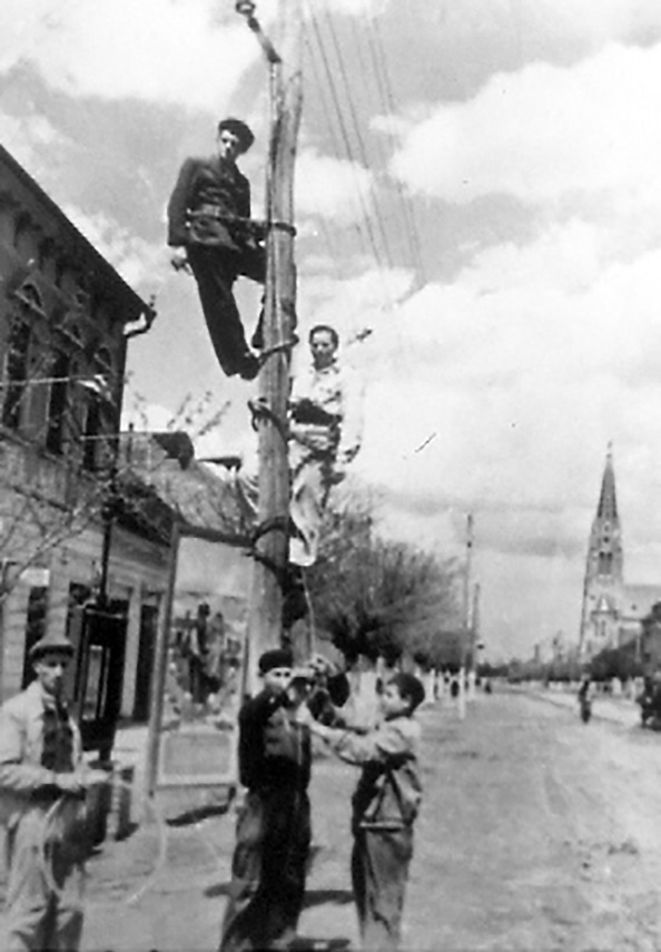 School Sister of Notre Dame (second from top) and coworkers repairing telephone lines in Romania.