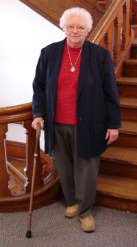 Sister Mary Luke Baldwin standing with cane in Notre Dame Hall next to staircase.